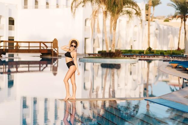 Modello grazioso, ragazza che indossa occhiali da sole alla moda, cappello di paglia, costume da bagno nero in posa in mezzo alla piscina. ottimo periodo estivo, vacanze, vacanze, fine settimana termale.