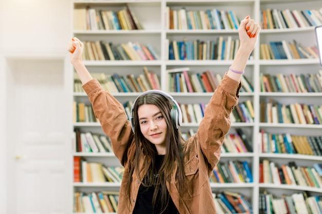 Довольно современная уверенная 25-летняя девушка с длинными каштановыми волосами слушает любимую музыку в наушниках, поднимает руки и позирует возле книжных полок в библиотеке