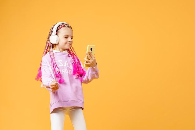 笑顔のヘッドフォンでピンクのドレッドヘアを持つかなり現代的な女の子