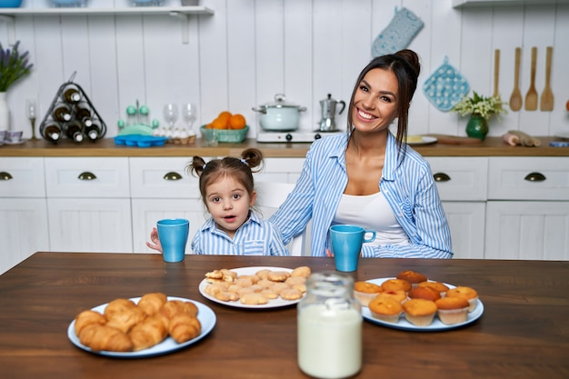 Pretty mom and her little daughter have breakfast in the kitchen.