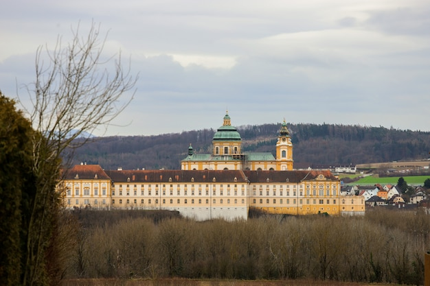 Pretty monastery among the autumn trees and a field of cultivation. melk abbey.