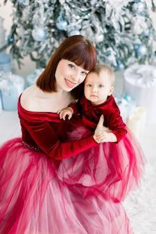 예쁜 엄마와 그녀의 작은 딸, 빨간 드레스를 입고, 크리스마스 트리