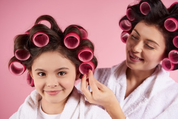 Pretty mother and daughter in hair curlers