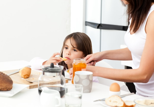 Довольно мать, давая тост с вареньем дочери на завтрак
