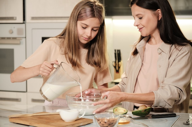 Pretty mother and her cute teenage daughter standing by table in the kitchen and pouring milk into bowl while prparing icecream