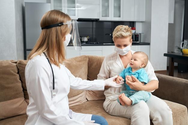 의사 근처에 앉아있는 동안 그녀의 아들을 들고 예쁜 어머니