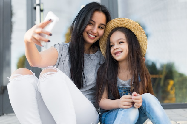 Pretty mother and little daughter make selfie photo by smartphone
