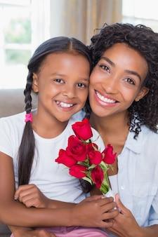 장미를 들고 딸과 함께 소파에 앉아 예쁜 어머니