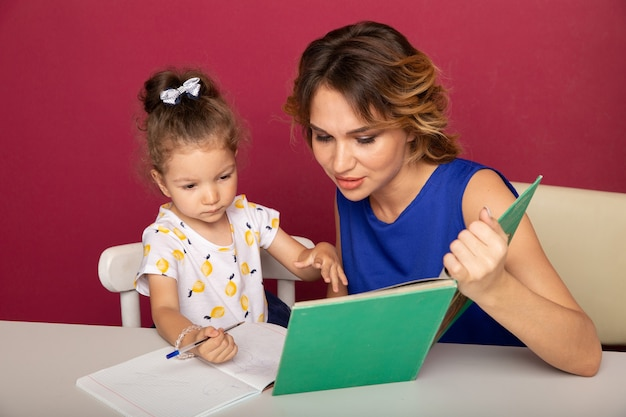 Pretty mother with cute daughter sitting with book in the room at home.