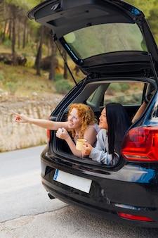 Pretty multiethnic girlfriends in open machine trunk