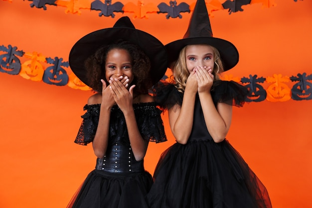 Pretty multinational girls in black halloween costumes laughing and covering their mouths isolated over orange pumpkin wall