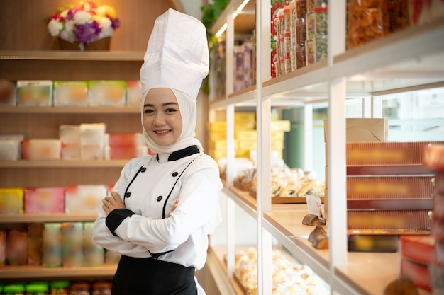 Pretty muslim asian woman with chef uniform wearing hijab crossed her arm in front of the shop. muslim small business owner