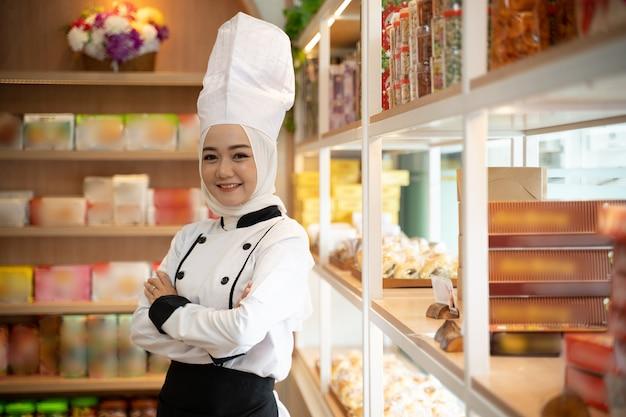 ヒジャーブを着たシェフの制服を着たかなりイスラム教徒のアジア人女性が店の前で腕を組んだ。イスラム教徒の中小企業の所有者