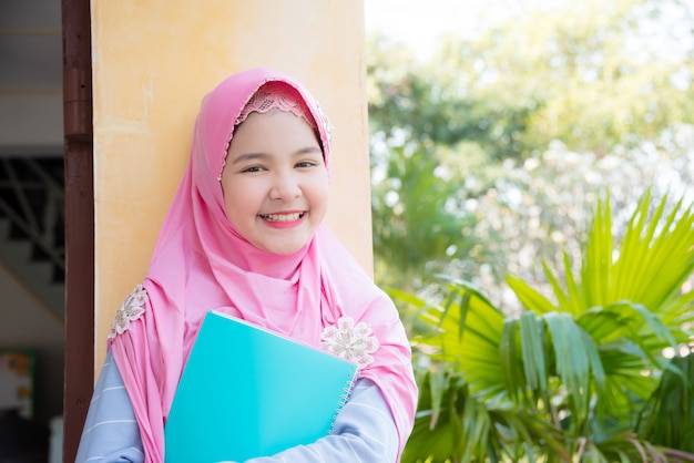 Pretty muslim girl holding book and smiles at school.