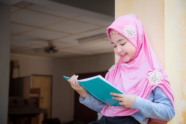 Pretty muslim girl reading book and smiles.