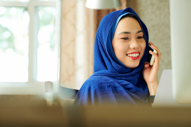 Pretty muslim woman calling on phone