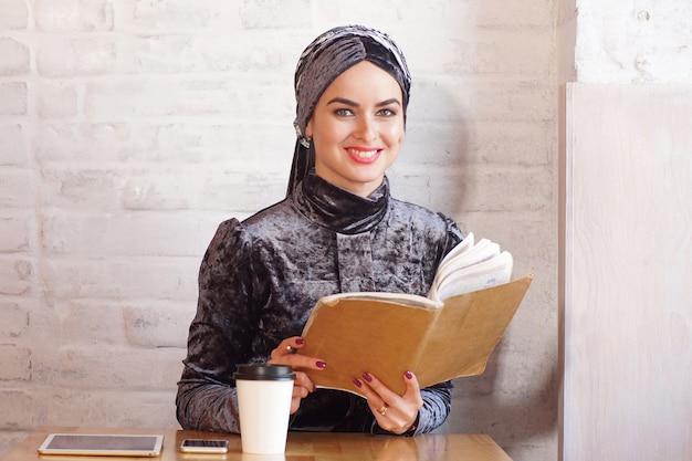かなりイスラム教徒の女性は本を保持し、カフェでカメラのためにポーズ