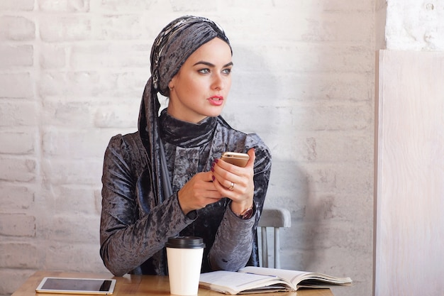 Pretty muslim woman holds a phone in her hands while sitting in cafe