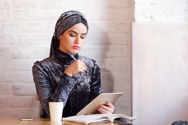 Pretty muslim woman holds a tablet in her hands while sitting in cafe