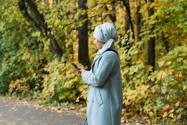 야외에서 휴대전화를 사용하는 예쁜 이슬람 여성. 스마트폰을 사용하여 히잡을 쓴 아랍 여성. 도시 공원에서 문자 메시지를 보내는 이슬람 소녀. 복사 공간