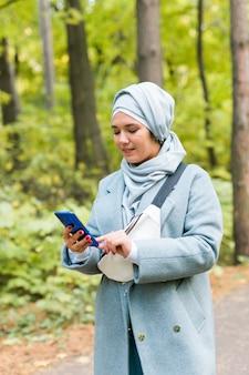 야외에서 휴대전화를 사용하는 예쁜 이슬람 여성. 스마트폰을 사용하여 히잡을 쓴 아랍 여성. 도시 공원에서 문자 메시지를 보내는 이슬람 소녀.