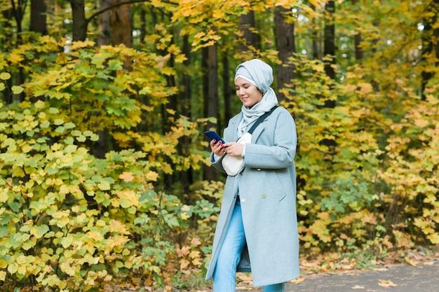 스마트폰 이슬람을 사용하여 히잡을 쓰고 휴대 전화를 사용하는 예쁜 이슬람 여성 야외 아랍어 여성