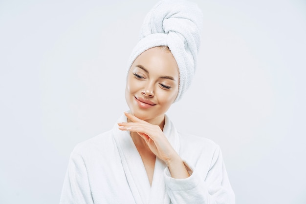 Pretty natural woman touches gently jawline, wears bath towel wrapped on head, dries hair after shower, cares about body, has clean skin, prepares for evening party, dressed in domestic robe