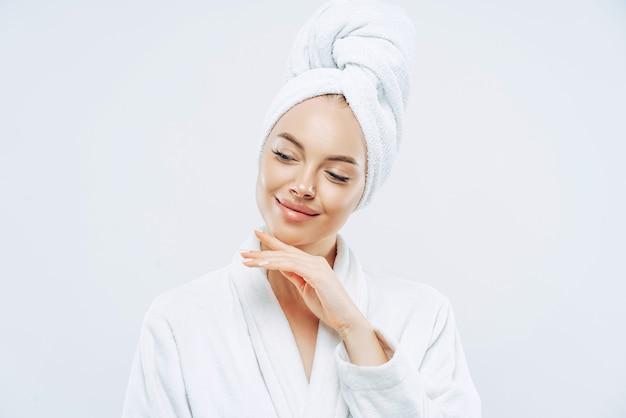 Симпатичная натуральная женщина нежно трогает линию подбородка, носит банное полотенце, обернутое на голову, сушит волосы после душа, заботится о теле, имеет чистую кожу, готовится к вечеринке, одета в домашний халат.