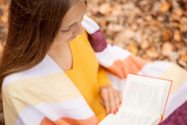 느슨한 머리를 가진 꽤 깔끔한 소녀는 책을 읽고 그녀의 어깨에 담요와 함께을 공원에서 벤치에 앉아. 자연의 여가, 지식 습득.