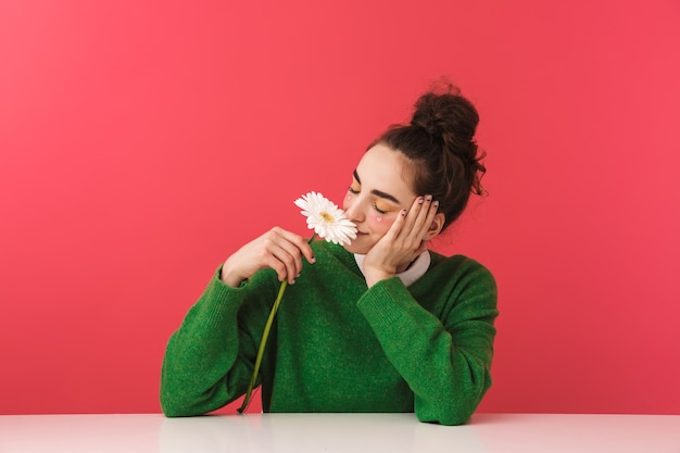 Девушка довольно ботаник сидит за столом изолированно, держа ромашку