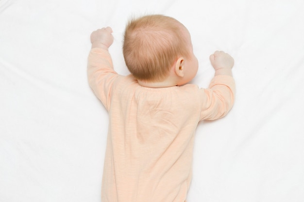 A pretty newborn baby in a beige bodysuit is lying on her stomach on a light blanket