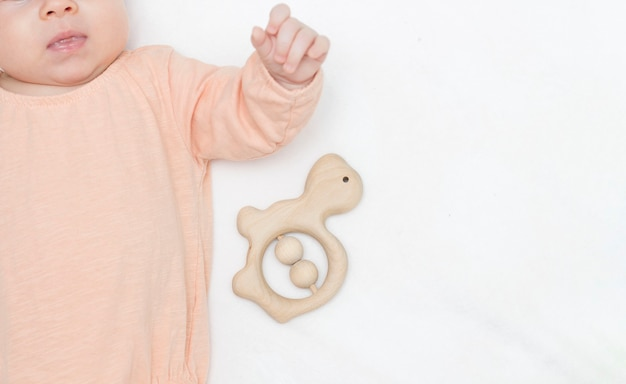 A pretty newborn baby in a beige bodysuit is lying on a light blanket next to a wooden rattle