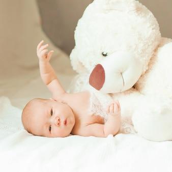 담요에 누워 큰 부드러운 장난감 예쁜 갓난 아기 소녀. 복사 공간이 있는 사진