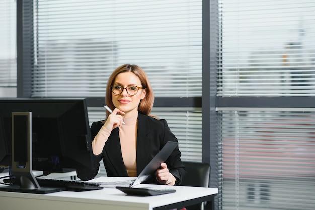 예쁜, 멋지고, 귀엽고, 완벽한 여자가 작업장의 가죽 의자에 책상에 앉아 안경을 쓰고 정장을 입고 테이블에 노트북과 노트북을 가지고 있습니다.