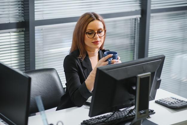 Симпатичная, милая, милая, идеальная женщина, сидящая за своим столом на кожаном кресле на рабочем месте, в очках, официальной одежде, с ноутбуком и блокнотом на столе
