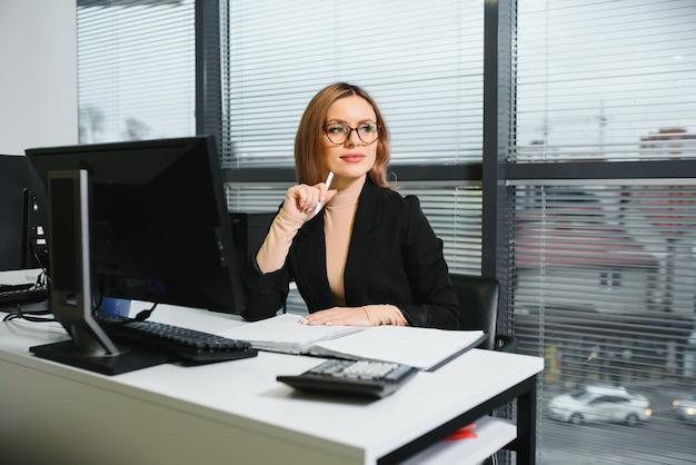 Симпатичная, милая, милая, идеальная женщина, сидящая за своим столом на кожаном кресле на рабочем месте, в очках, официальной одежде, с ноутбуком и блокнотом на столе Premium Фотографии