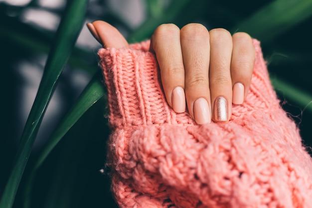 Красивый маникюр нюдового цвета, блестящий золотой палец на вязаном розовом шерстяном фоне