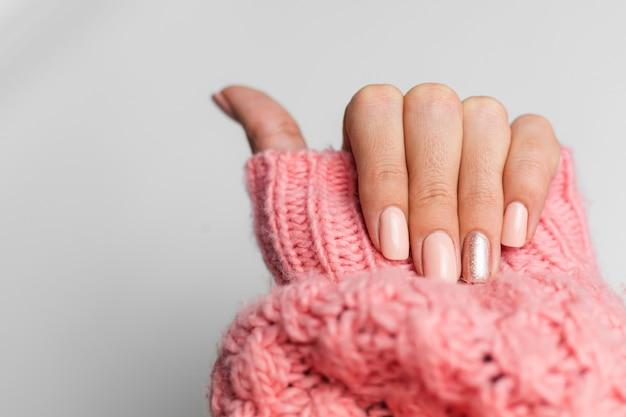 예쁜 누드 컬러 매니큐어, 한 손가락 반짝 이는 황금색, 니트 핑크 양모 필 오버 배경에