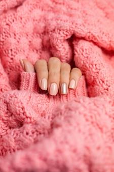 かなりヌードカラーのマニキュア、1本の指の光沢のある金色、ニットのピンクのウールの枕カバーの背景