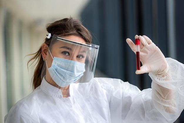 호흡기 코로나 바이러스 질병 2019에 대한 분석을 위해 혈액이 담긴 테스트 튜브를 들고 흰색 의료 제복을 입은 예쁜 간호사