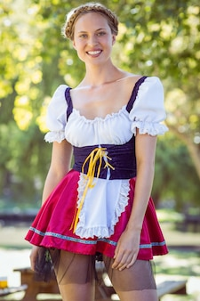 Pretty oktoberfest blonde smiling in the park on a sunny day