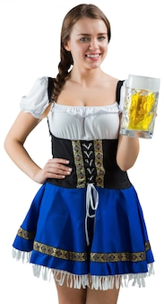 Pretty oktoberfest girl smiling at camera holding beer on white background