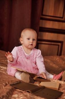 Симпатичная годовалая девочка в розовом платье со старой книгой сидит на кровати в комнате. ребенок в интерьере спальни. концепция образования и воспитания детей. фон для сайта или баннера. копировать пространство