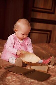 Симпатичная годовалая девушка в розовом платье со старой книгой сидит на кровати в комнате