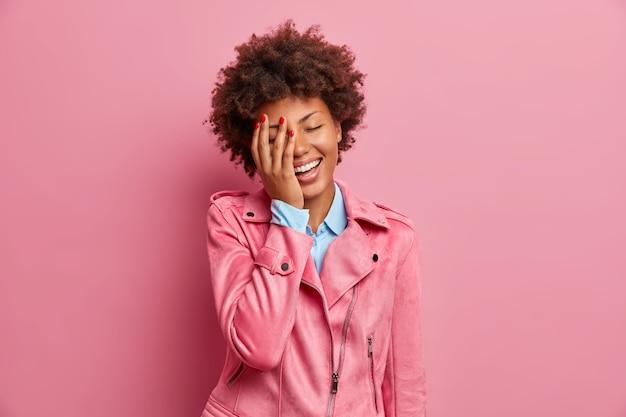 Довольно обрадованная молодая афроамериканка делает лицо ладонью и радостно смеется, выражая положительные эмоции