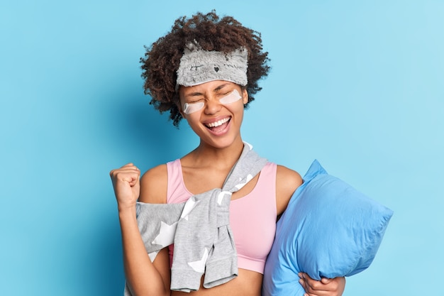 Pretty overjoyed curly haired girl clenches fist with joy celebrates finally reaching goals finds out positive news wears nightclothes has cheerful expression holds pillow isolated on blue wall