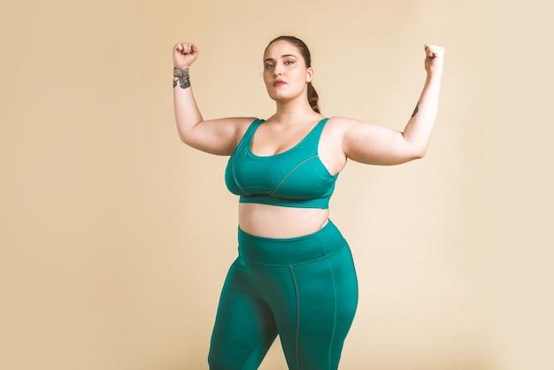 スタジオでポーズをとるスポーツウェアを着ているかなり特大の女性