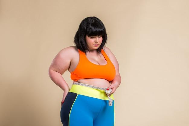 Pretty oversize woman wearing sportswear posing in studio