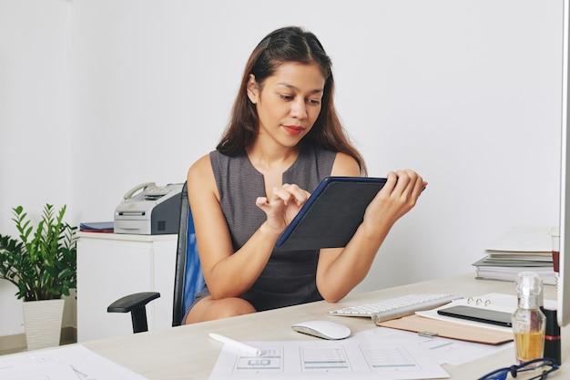 かなり物思いにふける若い多民族のuiデザイナーがオフィスの机に座って、彼女が作成したアプリケーションインターフェイスをテストしています