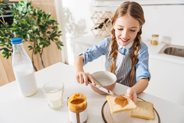 꽤 완벽합니다. 앞치마를 입고 부엌 테이블에 서있는 동안 자신과 형제 자매를 위해 아침 식사를 요리하는 사랑스러운 화려한 소녀
